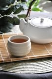 Tea Pot with a Cup of Hot Tea on Bamboo Mat. White tea pot with a cup of hot tea put on bamboo mat royalty free stock photography