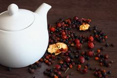 White tea pot and sweet dried fruits and berries on dark brown wooden table. Natural rustic breakfast. Royalty Free Stock Image