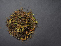 White tea. Leaves lying on an elegant black background - lots of copy space Stock Image