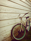 White and Teal Beach Cruiser Bike Beside White Painted Wooden Wall Stock Photos