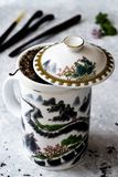 White teapot with 'great wall' design, tea herb, delicate background royalty free stock photos