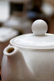 White teapot blurred background. Focus on white teapot top and spherical handle, with blurred brownish background royalty free stock photo