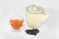 White teapot, a cup of tea and dried tea leaves. Stock Photos
