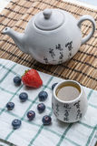 White teapot with cup of tea on the mat and white towel with some blueberries and strawberry. White teapot with cup of tea on the woven mat and white towel with Royalty Free Stock Photography