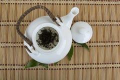White teapot with dry black tea leaves Stock Photos