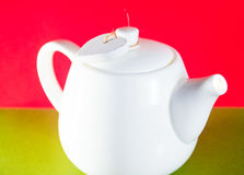 White teapot with heart tied with a cord isolated on red background. Love tea. White teapot with heart tied with a cord isolated on background. Love tea Royalty Free Stock Photography
