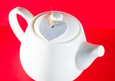 White teapot with heart tied with a cord isolated on red background. Love tea.  Stock Photos