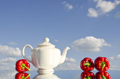 White teapot and red peppers Stock Photography
