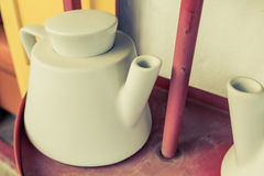 White teapot on the red shelf  with vintage filter. Royalty Free Stock Photography