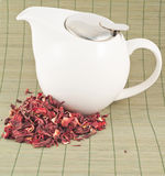 White teapot with red tea. White teapot with the heap of red tea over bamboo mat Royalty Free Stock Images