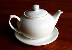 White teapot and the saucer on the wooden table alone close up. One white teapot and the saucer on the wooden table Stock Photography