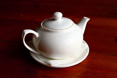 White teapot and the saucer on the wooden table alone. One white teapot and the saucer on the wooden table Royalty Free Stock Images