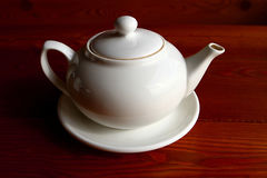 White teapot and the saucer on the wooden table alone Stock Photography