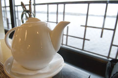 White teapot on a table in restaurant Royalty Free Stock Image