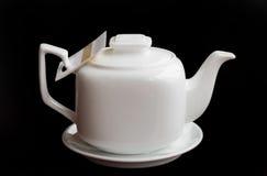 White teapot on a black background. White teapot with tea on a black background Stock Images