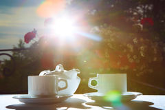 White teapot, two cups and sun. Garden party. White teapot, two cups and sun. Garden party Stock Photography
