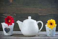 White teapot and yellow red flower Royalty Free Stock Photos