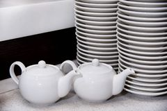 White teapots and high stacks of plates royalty free stock images