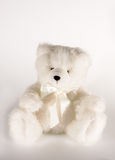 White teddy. Cuddly teddy bear looking very soft and fluffy and wearing a bow tie Royalty Free Stock Photos