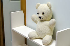 White Teddy Bear. Sad white teddy bear on a self outside a children room at home stock photo