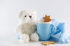White Teddy bear, blue mug and cookies on white background. Christmas composition royalty free stock image