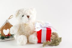 White Teddy bear, Christmas toys and red gift box. On white background stock images