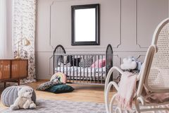 White teddy bear on the floor of stylish baby room interior with grey wooden crib with pillows, white rocking chair and mockup stock images