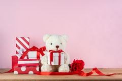 White teddy bear and gift boxes. White teddy bear holding gift box and pile of gifts on wooden table on pink background stock photography