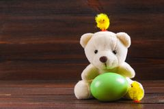 White teddy bear with a green Easter egg and chickens on a brown wooden table. White teddy bear with a green Easter egg and chickens on a brown wooden table Stock Images
