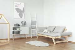 White teddy bear on grey sofa. With pillows next to white ladder and shelf with boxes royalty free stock image