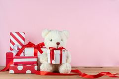 White teddy bear and gift boxes. White teddy bear holding gift box and pile of gifts on wooden table on pink background royalty free stock photo
