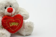 White Teddy bear holding red heart with text LOVE, isolated on white background Stock Photo