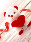 White teddy bear holding a red heart on white rustic wooden back Stock Photography