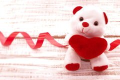 White teddy bear holding a red heart on white rustic wooden back Stock Images