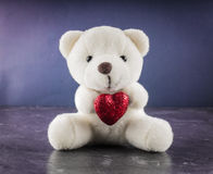 White teddy bear with love letter on red heart gray background. Say i you for valentine `s day concept. White teddy bear with love letter on red heart on gray royalty free stock photos