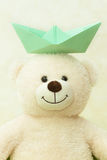 White teddy bear with a paper boat on a head Stock Image