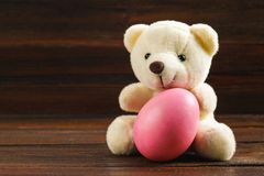 White teddy bear with a pink Easter egg on a brown wooden table. White teddy bear with a pink Easter egg on a brown wooden table Royalty Free Stock Images