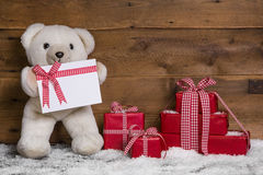 White teddy bear with red Christmas presents on wooden backgroun. Wooden christmas background with a teddybaer and red giftboxes Stock Photos