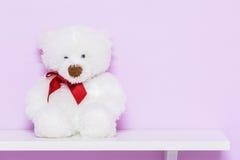White teddy bear on shelf. White doll bear on the pink background stock photo
