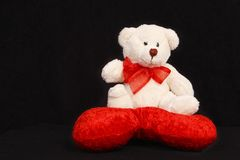 White teddy bear sitting on a heart shaped pillow Royalty Free Stock Images