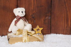 White teddy-bear sitting on present box for christmas. Wooden background royalty free stock photography