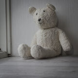 White teddy bear sitting sad one in the window Royalty Free Stock Image