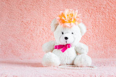 White teddy bear toy with orange flower barrette on head Stock Photography