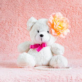 White teddy bear toy with orange flower barrette on head Royalty Free Stock Photography