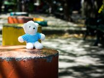 The white teddy bear wear a blue shirt and sitting on orange bench with cement. the background is public park. copy space for text. And content Stock Photography