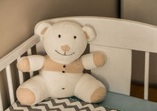 White teddybear on bed. White soft teddy bear sitting on a corner of a wooden baby bed Royalty Free Stock Photo