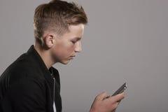 White teenage boy using mobile phone, waist up, side view Stock Image
