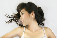White teeth. Pretty chinese girl lying down relax Royalty Free Stock Photo