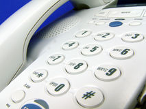 White telephone. With blue background royalty free stock image