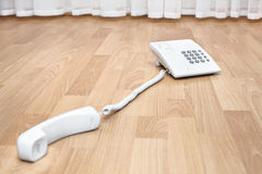 White telephone on the parquet Royalty Free Stock Image